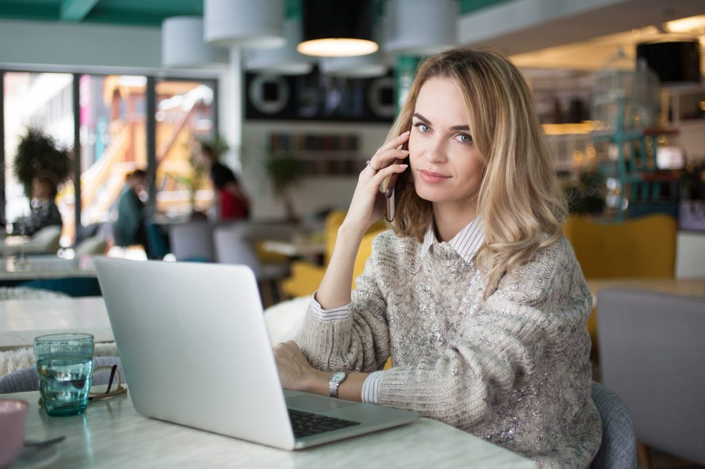 Portrait of beautiful female manager talking on phone. Confident young business lady calling colleague from cafe. She sitting at table with open laptop and looking at camera. Businesswoman concept